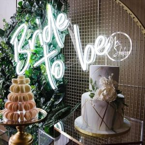 Large Bride to Be Wedding Sign in Bright LED Neon shown mounted on wire mesh behind the wedding cake - photo from CustomNeon.com