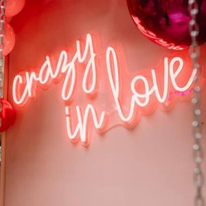 Crazy in Love LED neon light shown mounted on a wall with balloons - photo from CustomNeon.com