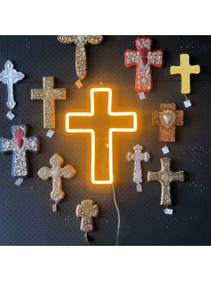 LED neon cross shown illuminated in yellow, wall mounted and surrounded by ornate crosses - photo from CustomNeon.com