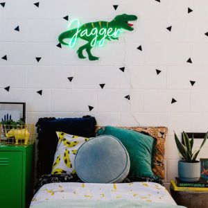 Personalized LED neon child's name sign with dinosaur background shown in child's bedroom- from CustomNeon.com