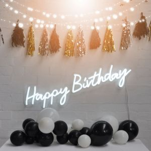 * Happy Birthday * is a lightweight, portable neon sign in modern cursive font, shown against a brick wall. Photo from CustomNeon.com