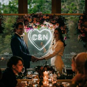 Beautiful LED neon heart light personalized with the bride & groom's initials. Shown here on a mesh background with the happy couple. Photo from CustomNeon.com
