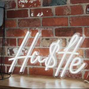 Hustle Neon Sign shown on an exposed brick wall  - photo from CustomNeon.com