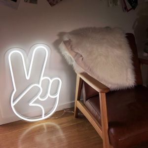 Lighted Peace Sign Hand Emoji shown against wall in a living room - Photo CustomNeon.com