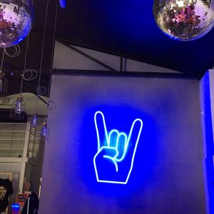 Rock On Emoji LED Neon Sign shown in blue, wall mounted in a fashion store - photo from CustomNeon.com